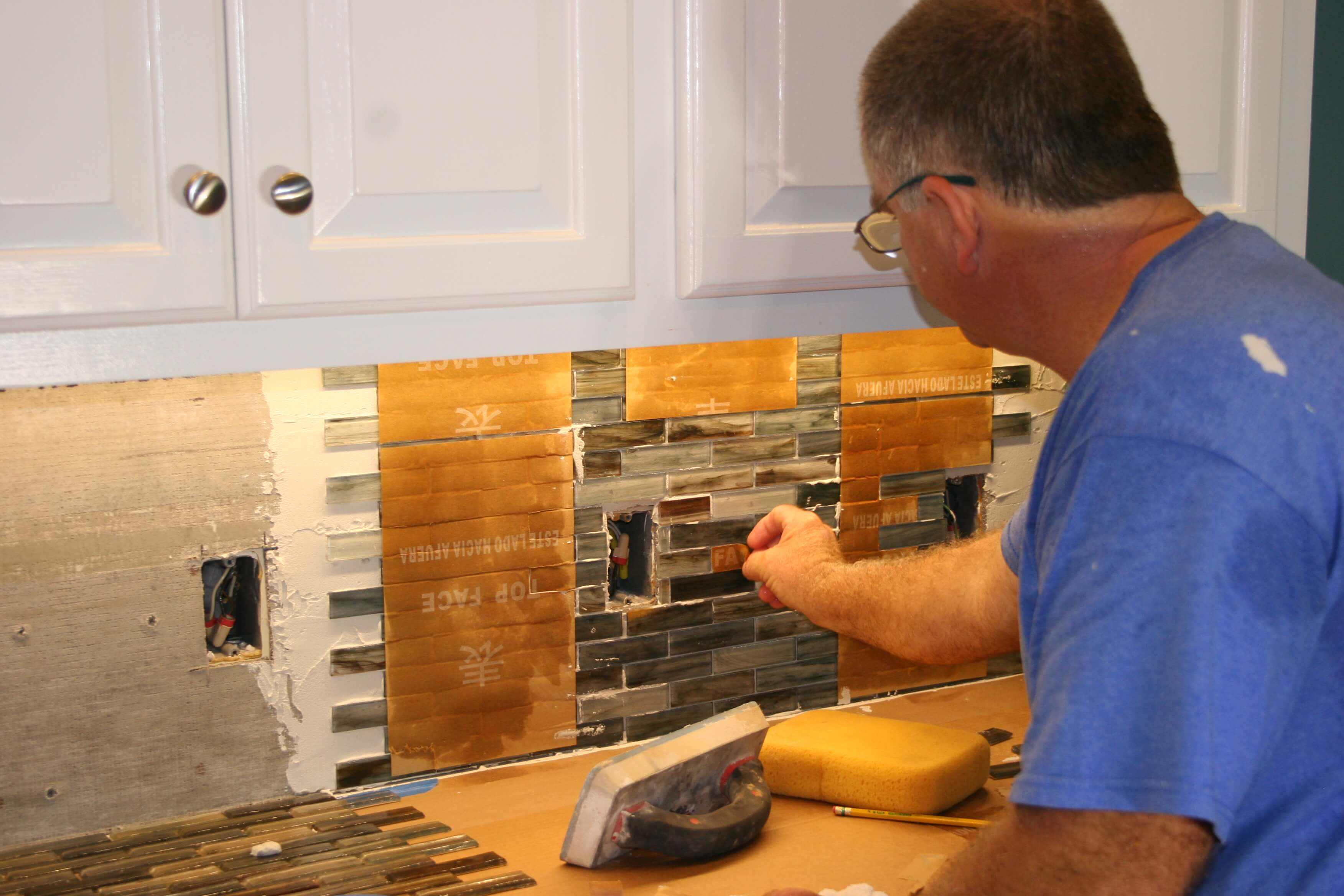 contractors applying tile backsplash